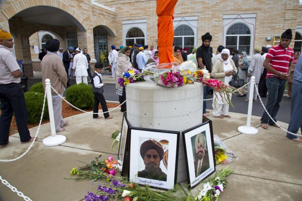 People walk around a flag pole memorial outside the Sikh Temple of Wisconsin in Oak Creek, Wisconsin, the site of a hate-fueled, violent attack that left six members of the Sikh community dead.