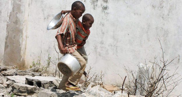 Two Somali children carrying a bowl and a pot walk to a food distribution center. As the election gets closer, the media must force politicians to discuss poverty and hunger, both in America and abroad.
