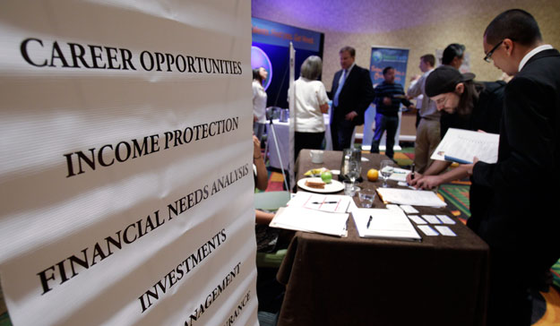 People looking for work talk at a Primerica job booth at a job fair in San Jose, California. The economy continued to make gains in September but remains sluggish in some areas.