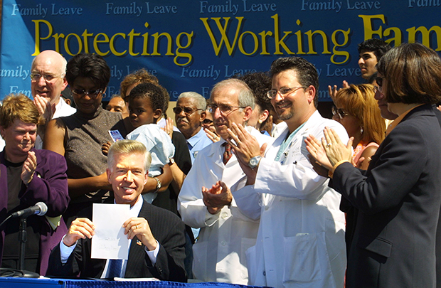 Then-Gov. Gray Davis (D-CA) holds up the paid family leave bill, Senate Bill 1661, after signing it during a news conference at the University of California, Los Angeles, Monday, September 23, 2002, in the Westwood area of Los Angeles.