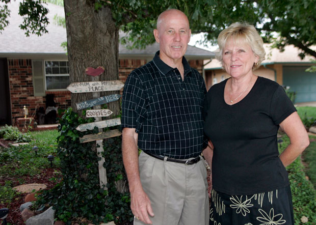 Retirees Rick Corley, left, and his wife Jean pose for a photo in front of their home in Moore, Okla.