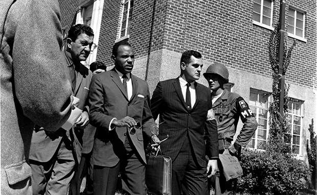 In this October 2, 1962, file photo, James Meredith, center with briefcase, is escorted to the University of Mississippi campus in Oxford. Escorting Meredith is Chief U.S. Marshal James McShane, left, and an unidentified marshal at right.