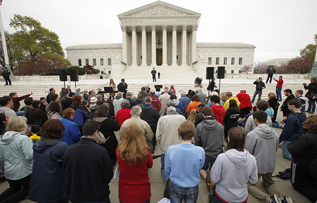"Members of Christian faith organizations kneel in prayer in front of the U.S. Supreme Court in Washington as part of ""Encircle the Court in Prayer,"" on the eve of the Court's arguments on the Affordable Care Act, Sunday, March 25, 2012."