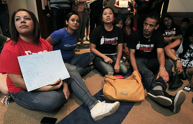 Yadira Garcia, left, of the Arizona Dream Act Coalition, holds up a sign in protest as she joins young immigrants as they sit in the waiting area of Gov. Jan Brewer's (R-AZ) office on Thursday, August 16, 2012, in Phoenix.