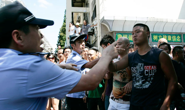 Protesters, right, confront with police officers, left, near the local government office building in July in Qidong, Jiangsu Province, China. Protests are becoming more commonplace, as Chinese citizens begin to demand higher quality of life from Communist Party officials.