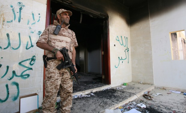 A Libyan military guard stands in front of one of the U.S. Consulate's burnt out buildings in Benghazi, Libya.