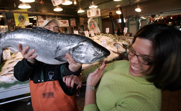 Fish vendor and customer with a 20 pound king alaskan salmon