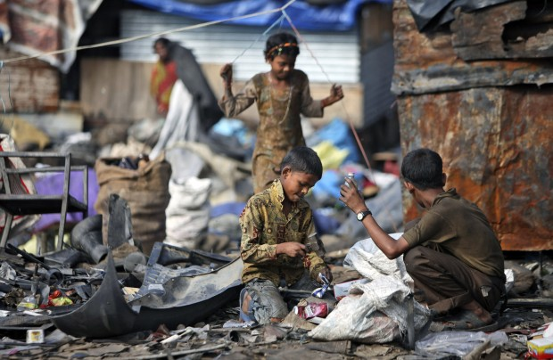 Ragpicker children collect recyclable materials at a yard on the outskirts of Jammu, India, Wednesday, Aug. 29, 2012.
