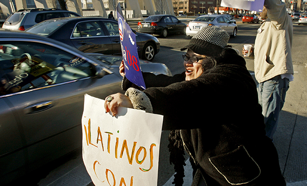 "Jackie Reyes holds a sign that says ""Latinos Con Obama,"" meaning ""Latinos with Obama"" in Spanish, and shouts to motorists in support of then-presidential hopeful Sen. Barack Obama (D-IL), Monday, February 11, 2008."