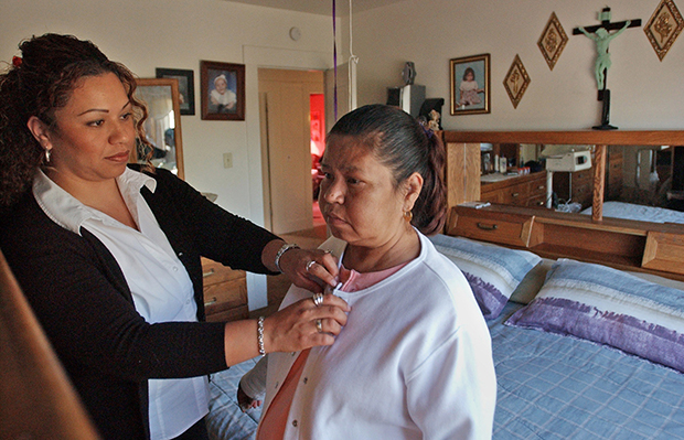 Elizabeth Gomez, left, assists her mother, Virginia Falcon, at home in Oakland, California.