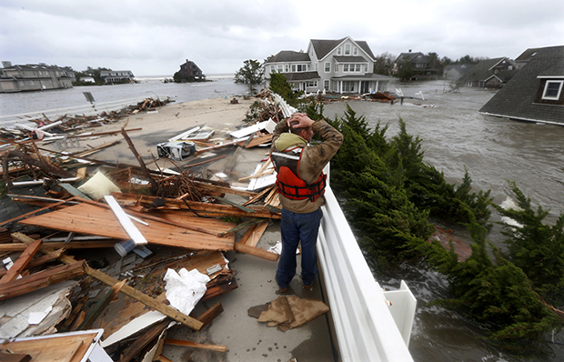Brian Hajeski, 41, of Brick, New Jersey, reacts as he looks at debris of a home that washed up on to the Mantoloking Bridge the morning after Hurricane Sandy rolled through, Tuesday, October 30, 2012, in Mantoloking, New Jersey.