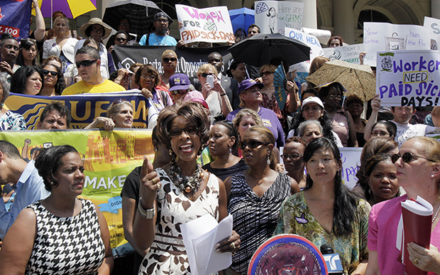 Marjorie Hill, second left, CEO of the Gay Men's Health Crisis, addresses the Women for Paid Sick Days rally on the steps of New York's City Hall, Wednesday, July 18, 2012. The lack of universal paid sick days exacerbates the vulnerabilities many gay and transgender people experience in the workplace.