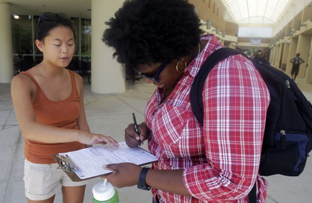 Aubrey Marks, left, helps a University of Central Florida student to register to vote in Orlando, Florida.