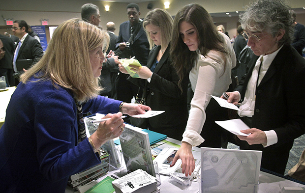 Patricia Mazza, left, meets job seekers during a National Career Fairs job fair in New York, Wednesday, October 24, 2012.