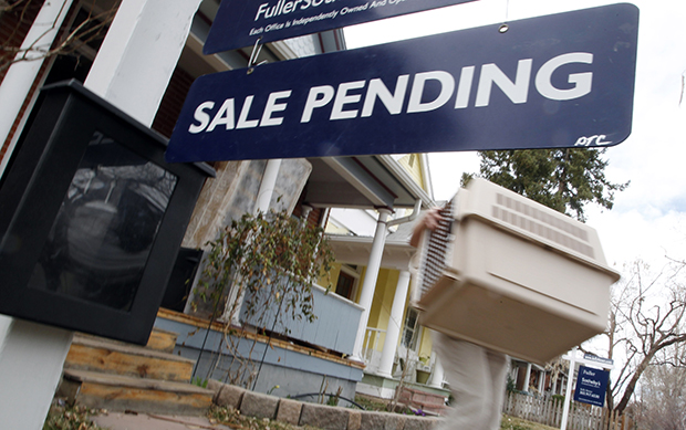In this Saturday, March 17, 2012, photo, a pending sale sign is seen outside a home on the market in south Denver, Colorado.