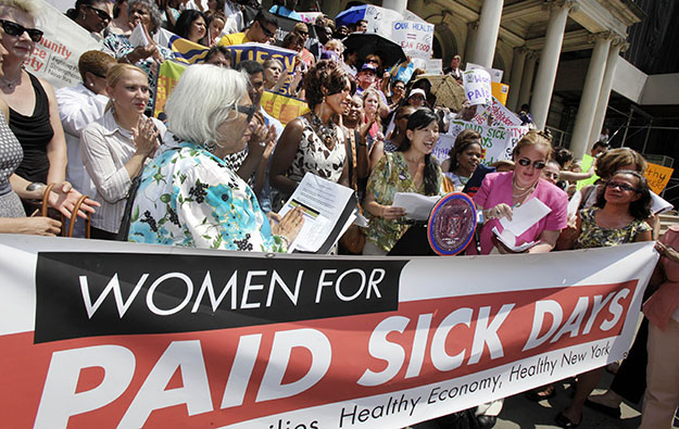 Ai-Jen Poo, center, Executive Director of the National Domestic Workers Alliance, reads her statement at a Women for Paid Sick Days rally on the steps of New York's City Hall on Wednesday, July 18, 2012.