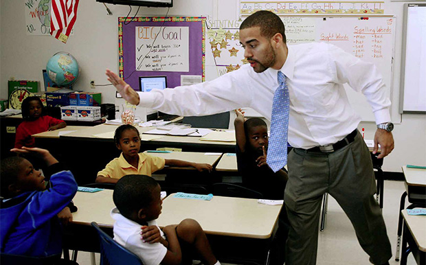 "In this photo taken September 1, 2011, teacher Michael Darmas ""high fives"" a student at Holmes Elementary School in Miami."
