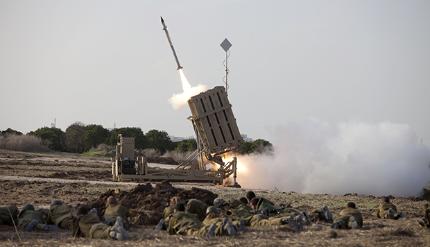 Israeli soldiers lie on the ground as an Iron Dome missile is launched near the city of Ashdod, Israel, Monday, November 19, 2012.
