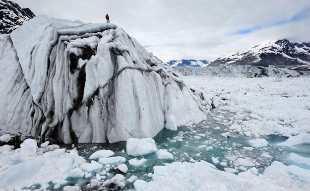 A hiker surveys the damage from climate change atop an iceberg in Alaska. Correcting climate change used to be a bipartisan effort, but recently has become more partisan, causing faith groups to get involved.