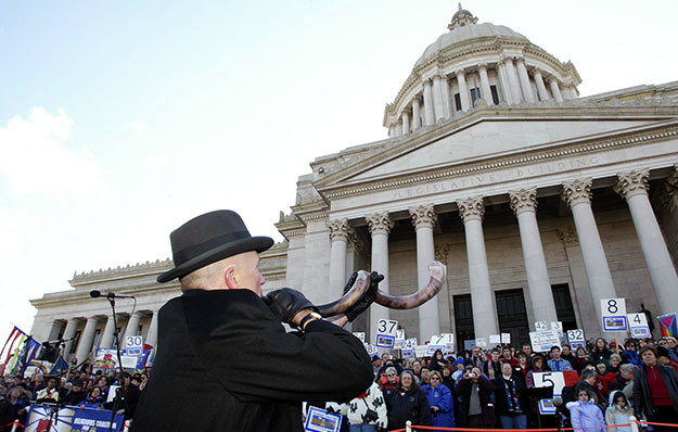 "Jon Lellelid, of the Temple De Hirsch Sinai in Seattle, blows a Shofar, or ""ram's horn"" at the Capitol in Olympia, Washington on Monday, Feb. 14, 2005 to close a Valentine's Day rally supporting equal marriage rights for same-sex couples. Approximately 700 people from across the state attended the rally, which was organized by the interdenominational Religious Coalition for Equality."