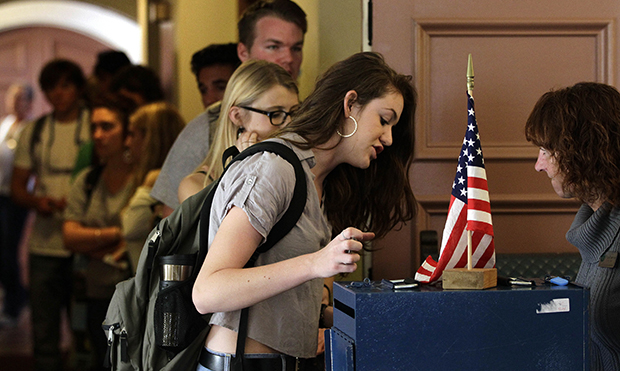 College student Cortney Ratashak, 18, of Littleton, Colorado, talks over paperwork with an electoral official before voting in the general election, at a polling station serving the local student population on the campus of the University of Colorado, in Boulder, Colorado, Tuesday, November 6, 2012.