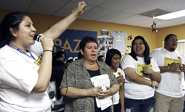 Grecia Lima, left, cheers as Maria Durand, second from left, brings her early voting ballot as they join members of Promise Arizona in Action in announcing their voter registration drive with Latino youth at a news conference, Thursday, October 25, 2012, in Phoenix.