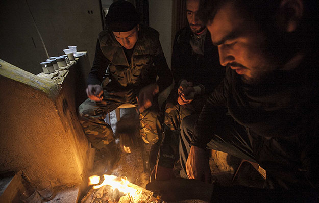 Syrian rebels make a fire to keep warm after clashes with troops loyal to Syrian President Bashar al-Assad at on the front line in Aleppo, Syria, on December 2, 2012.