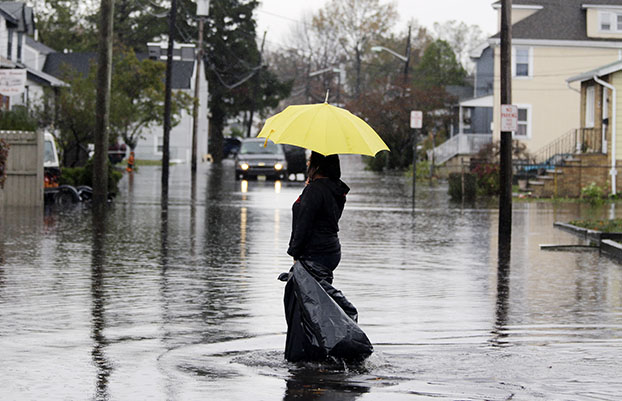 Lisa Torres walks along a flooded street to check the flood damage at her hair salon in the wake of superstorm Sandy on Tuesday, October 30, 2012, in Little Ferry, New Jersey. Sandy arrived along the East Coast and morphed into a huge and problematic system, putting more than 7.5 million homes and businesses in the dark and causing a number of deaths.
