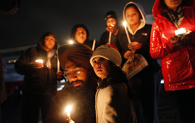 Eknoor Kaur, 3, stands with her father, Guramril Singh, during a candlelight vigil outside Newtown High School before an interfaith vigil with President Barack Obama, Sunday, December 16, 2012, in Newtown, Connecticut.