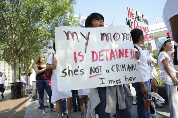Young person at a pro-immigrant rally holding a sign