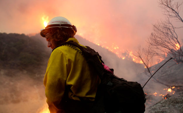 A wildlands firefighter stands in front of a wildfire