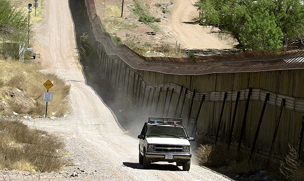 A U.S. Border Patrol agent patrols along the fence line of the U.S.-Mexico border in Nogales, Arizona.