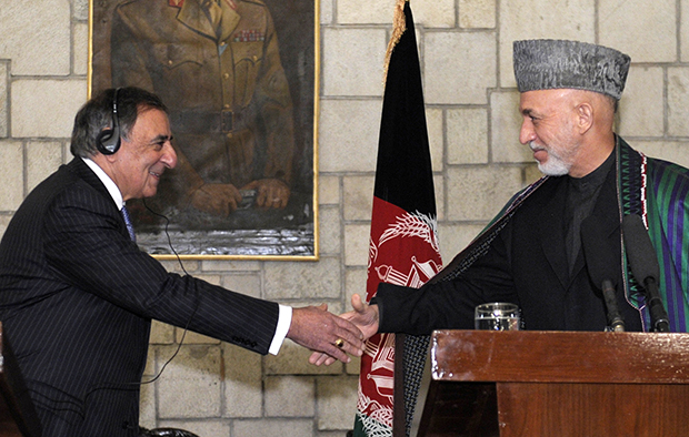 U.S. Defense Secretary Leon Panetta, left, shakes hands with Afghan President Hamid Karzai, right, during their joint press conference at the Presidential Palace in Kabul, Afghanistan, Thursday, December 13, 2012.