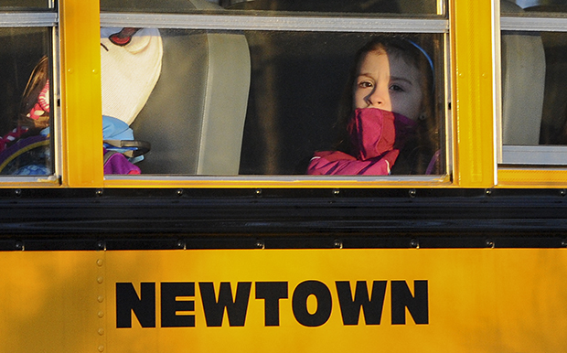 A girl sits on a Newtown bus leaving the new Sandy Hook Elementary School after the first day of classes in Monroe, Connecticut, Thursday, January 3, 2013.
