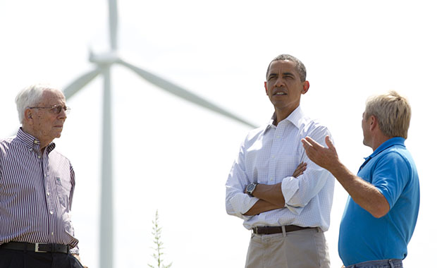 As wind turbines turn in the distance, President Barack Obama talks with Richard Heil, left, and Jeff Heil, on the Heil family farm, Tuesday, August 14, 2012, in Haverhill, Iowa, during a three-day campaign bus tour through Iowa.