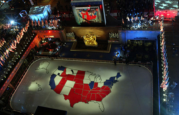 Workers walk on a giant presidential election map of the United States made of ice in the skating rink at Rockefeller Center, Tuesday, November 2, 2004, in New York.