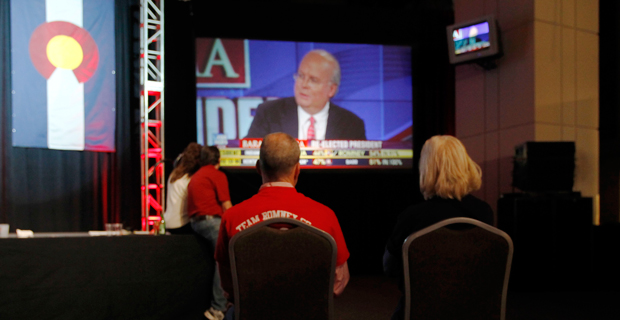 A couple watches Fox News commentator Karl Rove on a big-screen television during a Republican Party election night gathering on November 6, 2012.