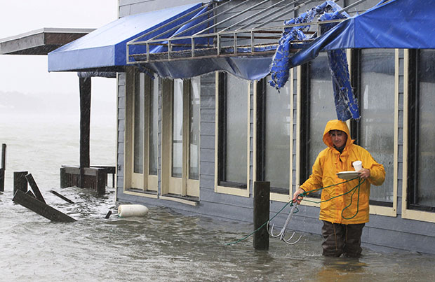 A worker retrieves a grappling hook on the dock next to Bubba's restaurant on the water in Virginia Beach, Virginia, Monday, October 29, 2012. Rain and wind from Hurricane Sandy flooded the business at high tide.
