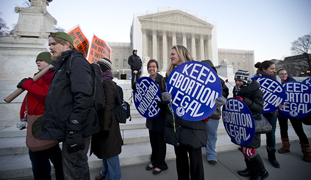 Bettina Hager, center, and Jeff Foster, left, join a candlelight vigil in front of the U.S. Supreme Court in Washington to commemorate the 40th anniversary of <em>Roe v. Wade</em>, the Supreme Court decision that legalized abortion, Tuesday, January 22, 2013.