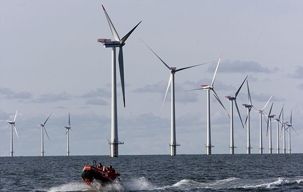A speed boat passes by offshore windmills in the North Sea offshore from the village of Blavandshuk near Esbjerg, Denmark. As America has stood on the sidelines, other countries such as Denmark, the United Kingdom, Germany, and even China have leapt ahead of us in developing offshore wind.