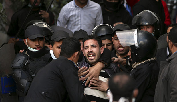 Egyptian riot police arrest a man during clashes with protesters near Tahrir Square in Cairo, Egypt, Wednesday, January 30, 2013.