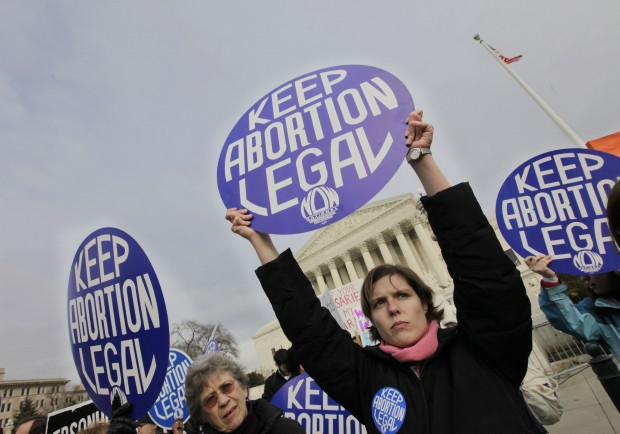 Abortion-rights activist and National Organization for Women (NOW) member Erin Matson, right, and others, holds up a signs