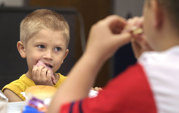 Christian Kellogg, 6, left, and his brother Anthony Kellogg, 9, eat lunch at King Elementary School in Des Moines, Iowa.
