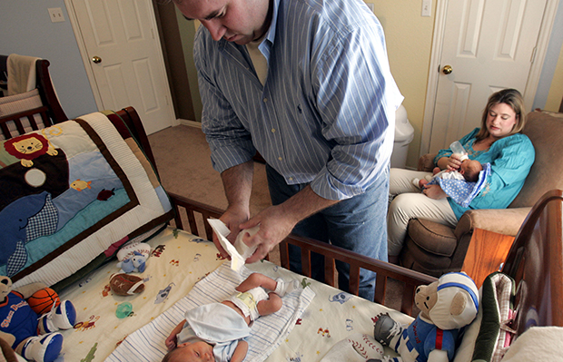 Tim Waddill changes Chase, his newborn twin son's diaper, left, as Stephanie Waddill, back, gives a bottle to their other twin boy, Connor, at their home in Irving, Texas, Friday, June 16, 2006.
