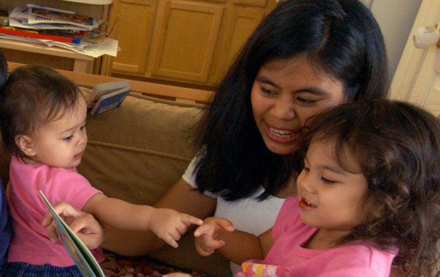 Maria Prince reads to her children Monica, 1 year old, and Olivia, 3 years old, in her home in Crofton, Maryland.