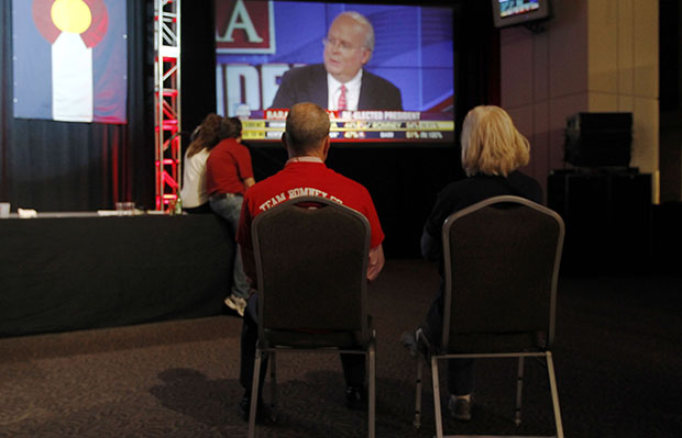 A couple sits on chairs in a near-empty room to watch Fox News commentator Karl Rove on a big-screen television during a Republican Party election night gathering in the club level of Sports Authority Field at Mile High in Denver, Colorado, on Tuesday, November 6, 2012.