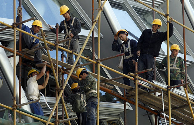 Workers stand on the scaffolding of a modern commercial building in Beijing, China, May 30, 2012.