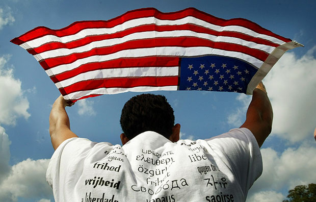 Juan Carlos Huezo Fuentes, who was born in El Salvador and now lives in San Jose, California, holds up a U.S. flag during a rally for immigrant rights in front of the Capitol Building in Washington, Thursday, October 2, 2003.