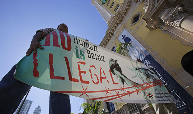 Immigration reform activists hold a sign in front of Freedom Tower in downtown Miami, Florida, Monday, January 28, 2013.
