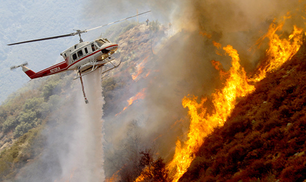 A Los Angeles County Firefighter helicopter drops water on a wildfire burning through 3,600 acres of the Angeles National Forest on Tuesday, September 4, 2012, near Glendora, California.